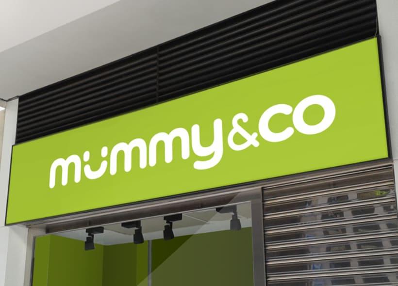 """Mummy&Co es el nombre de una franquicia de tiendas de ropa y accesorios para mamás y bebés. Una sonrisa sustituye la primera """"u"""" dándole un toque muy original y simpático. 0"""