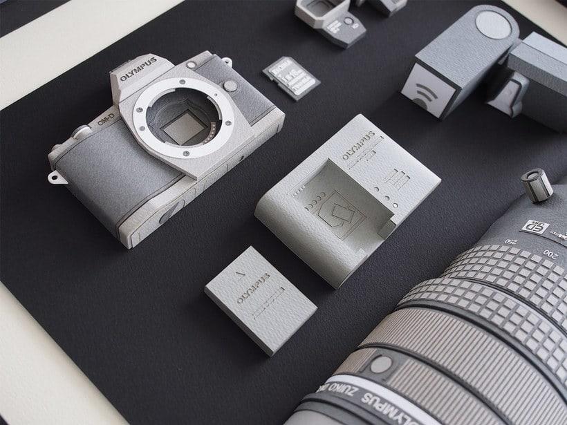 Papel, cúter y pegamento para construir una cámara fotográfica 3